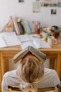 Image of a teacher leaning back at a desk with a book covering their face
